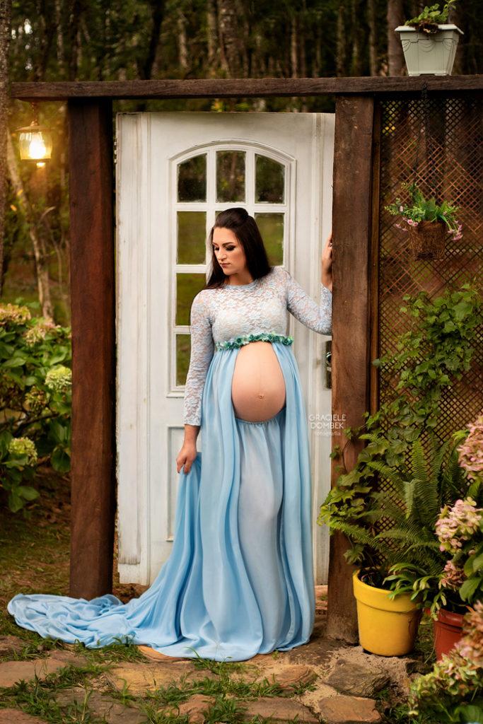 Gestante de vestido azul encostada na porta